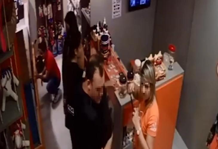 A suspeita aparece no fundo da imagem, vestida com uma camisa vermelha