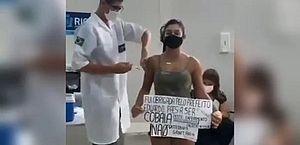 """Após passaporte, mulher se vacina no Rio com cartaz """"não à ditadura sanitária"""""""