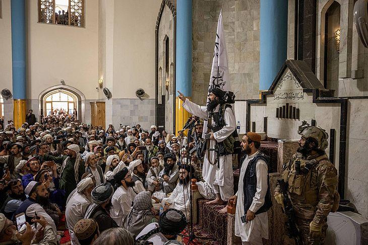 Ao lado de guarda-costas vestido com uniforme de soldado americano, líder talibã discursa armado com fuzil dos EUA