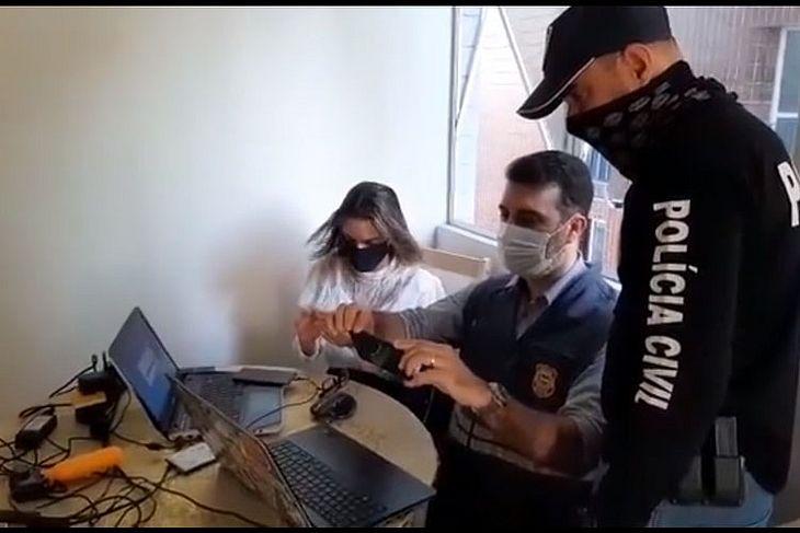Delegada Adriana Gusmão, junto com policial civil e perito do IC, examinam material apreendido